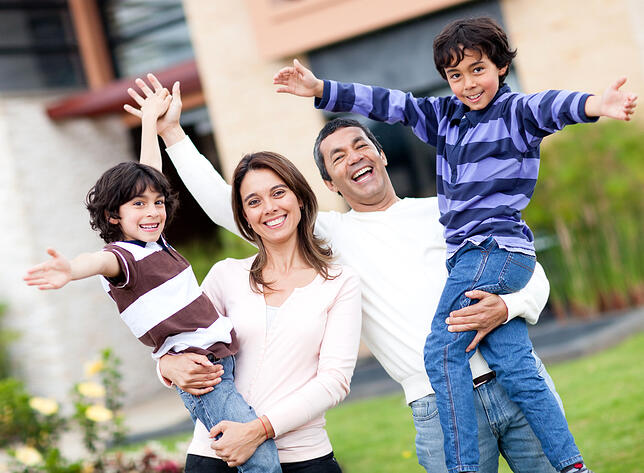 Excited family having fun outdoors with arms up
