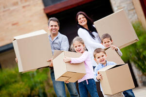 Happy family moving house and carrying boxes-1