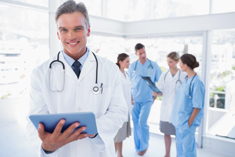 Smiling doctor holding digital tablet in front of his medical team